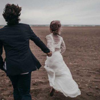 photo de mariés qui court sur la plage