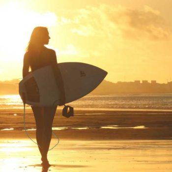 photo femme coucher de soleil avec planche de surf