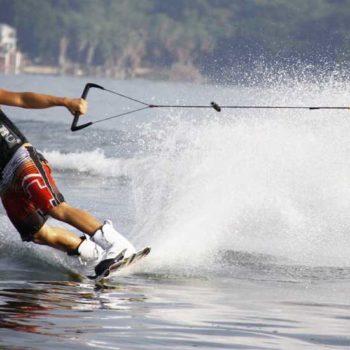 photo homme qui fait du surf tiré par un bateau