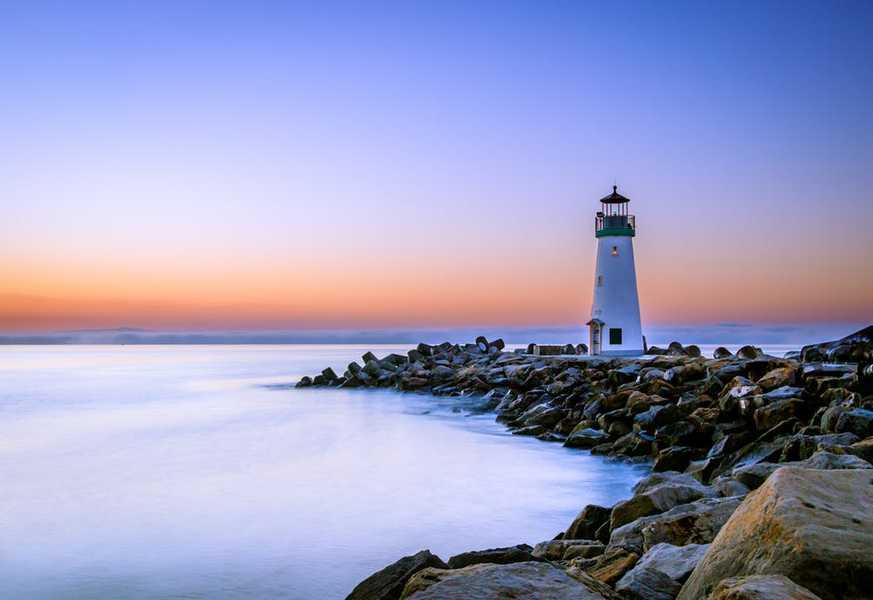photo phare bord de mer avec coucher de soleil sur les rochers