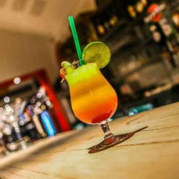 photo verre cocktail coloré avec paille et citron vert