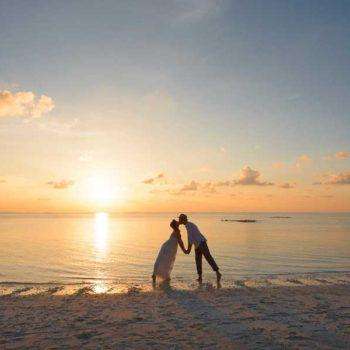 photo mariés qui s'embrassent sur la plage couché de soleil