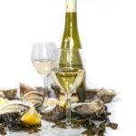 photo verre et bouteille de vin avec huitres algues et citron