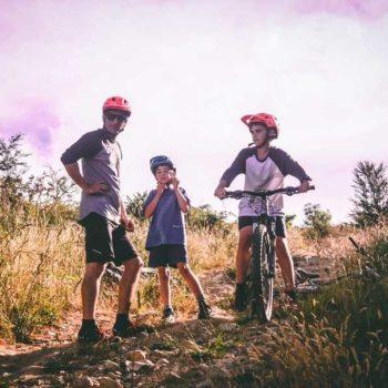 photo un père et ses deux fils avec casque de vélo dans la campagne
