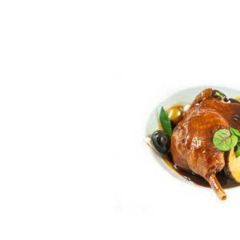 photo canard cuisine dans plat blanc avec des olives et champigons