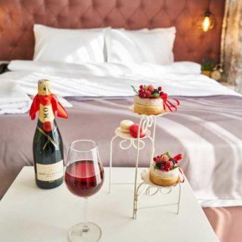 photo chmabre d'hotel romantique avec bouteille de vin de gateau gourmand