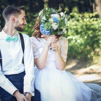 photo mariés chemin de foret assis, mariée qui se cache avec son bouquet
